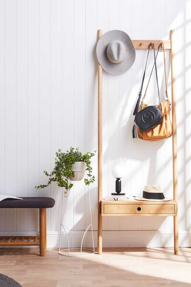 Arara de roupas com cabideiro completando a decor boho do quarto