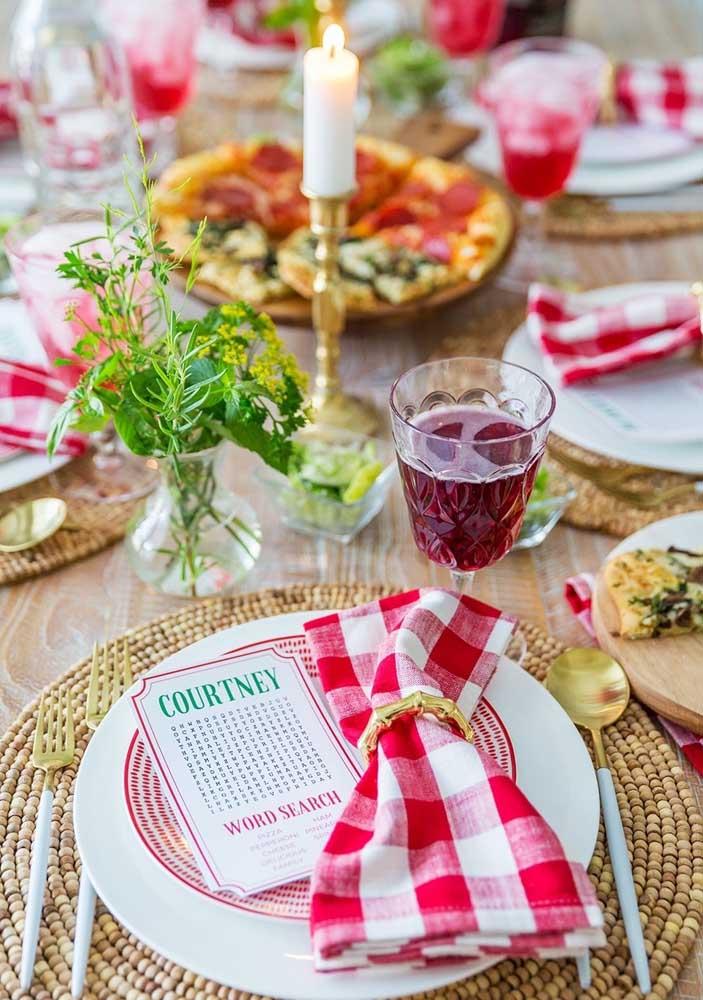 Mesa posta para a noite da pizza. Guardanapos xadrez, ervas frescas e candelabros para deixar o evento ainda mais temático