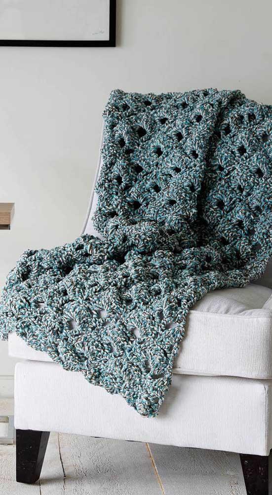 A poltrona branca ganhou vida com a manta de crochê mesclada em tons de azul e verde