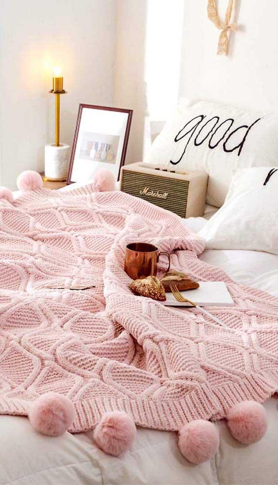 A manta de crochê rosa pode ser delicada ou moderna, dependendo do restante da decoração. Aqui, por exemplo, ela complementa um ambiente moderno em preto e branco