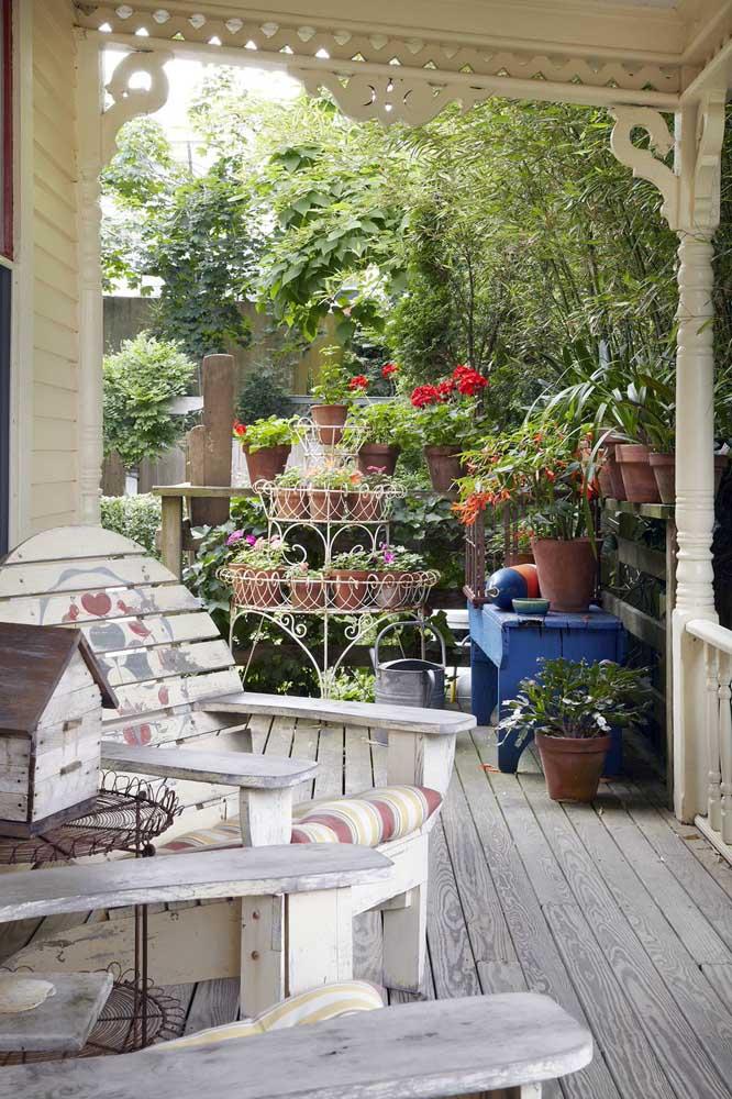 A varanda rústica e acolhedora apostou em um suporte grande de ferro na cor branca, remetendo a um estilo que lembra o provençal