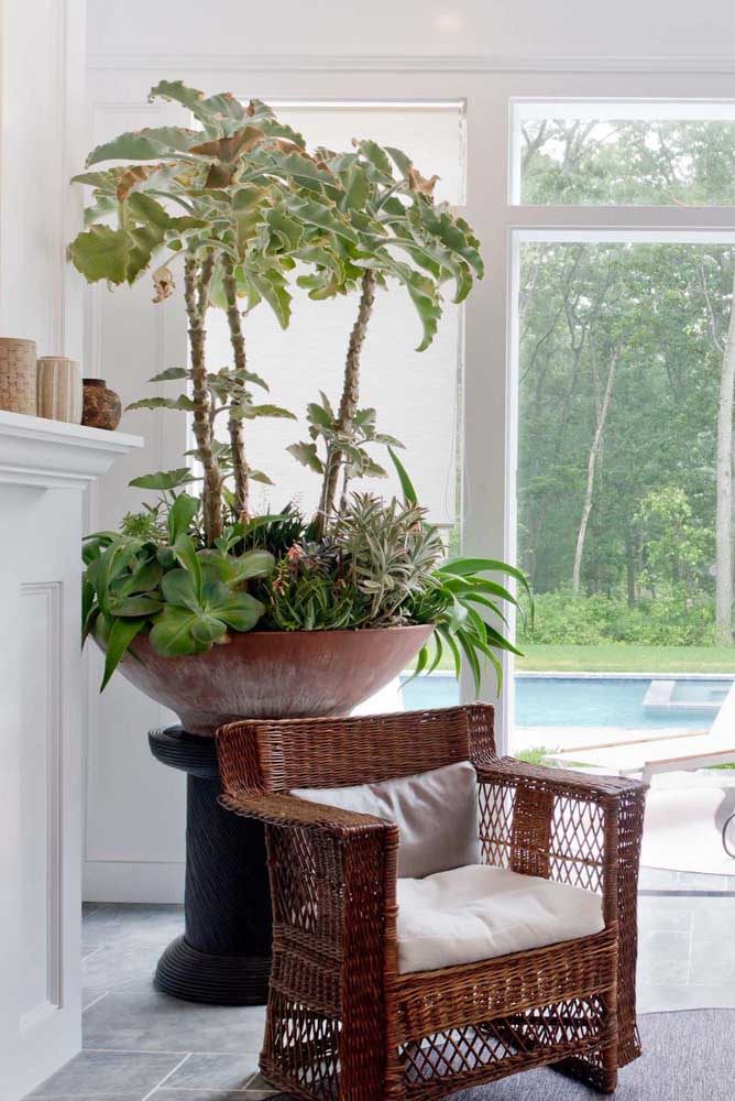 Nessa sala de estar, o suporte nada mais é do que um carretel de madeira. Perfeito para acomodar o vaso grande e pesado