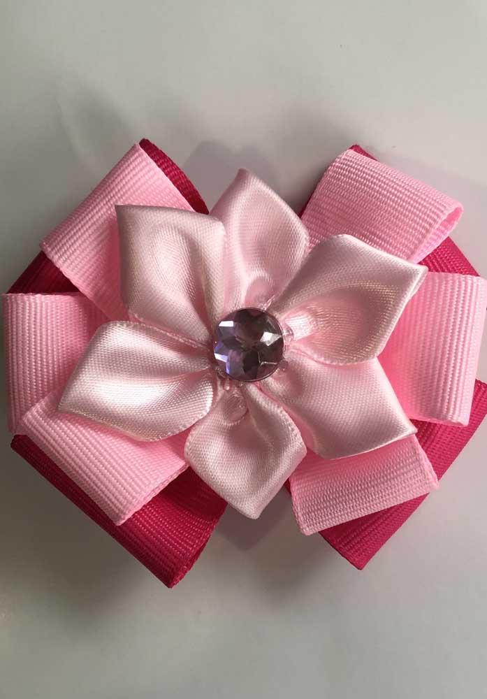 Laço de gorgurão em camadas com formato de flor. A pedrinha roxa faz a vez do miolo