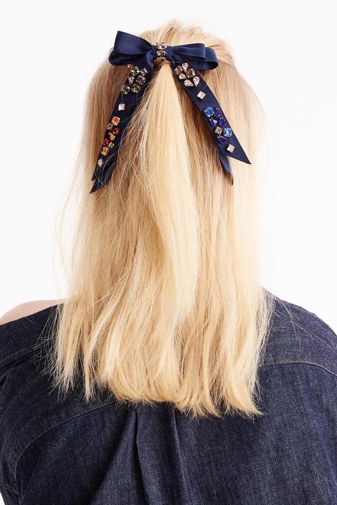 Nos cabelos claros, o laço de gorgurão escuro fica ainda mais destacado