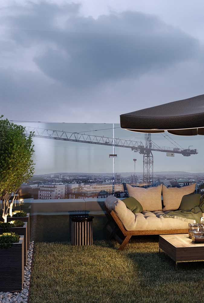 Terraço com grama sintética. A mobília fica protegida pelo ombrelone, já a segurança quem faz é a placa de vidro