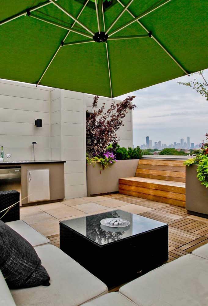 Terraço com espaço gourmet. O ombrelone garante a sombra no momento de servir a refeição
