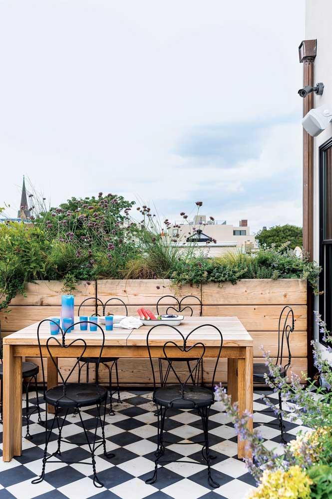 Terraço gourmet com ares provençais. A cerca viva com plantas e o piso xadrez se destacam nesse projeto