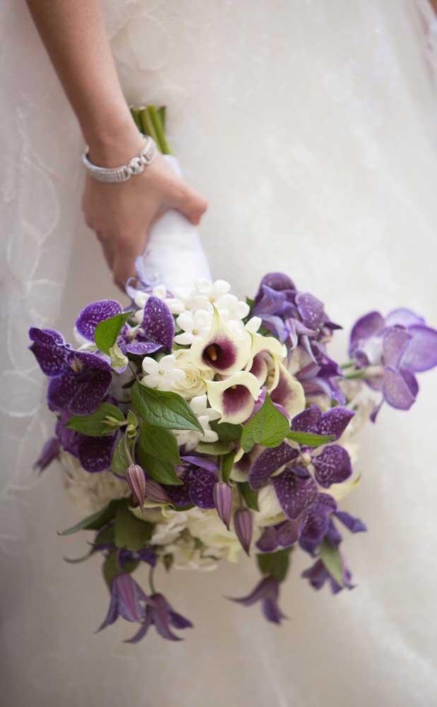 Diferente, esse buquê de noiva traz orquídeas roxas combinadas a delicadas flores brancas