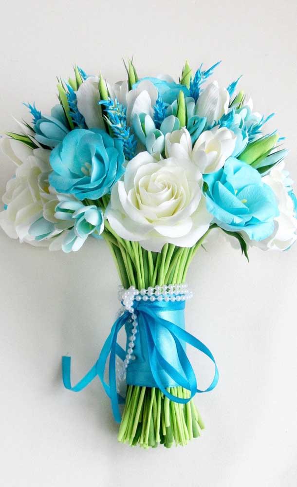 Buquê de flores azuis e brancas complementado pelo cordão de pérolas