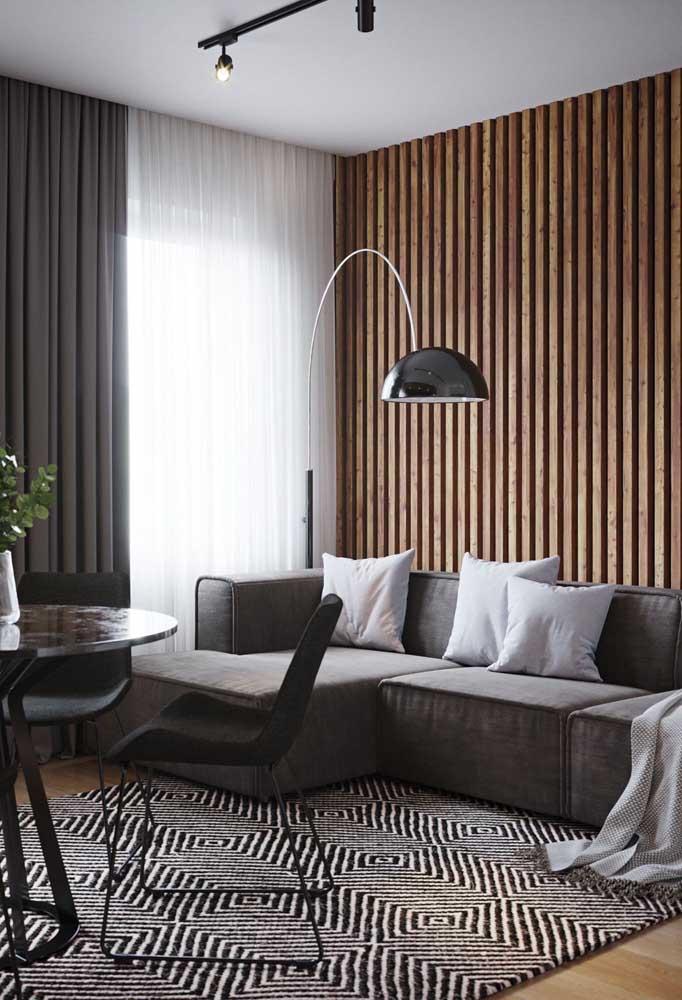 Tapete geométrico preto e branco na sala de estar. Repare que o restante da decoração acompanha a paleta de cores do tapete
