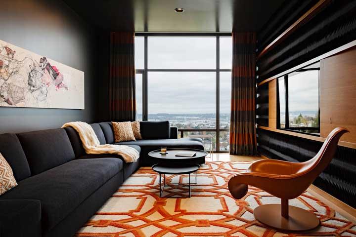 A sala ampla foi ainda mais valorizada com o tapete geométrico de fundo branco e linhas laranjas