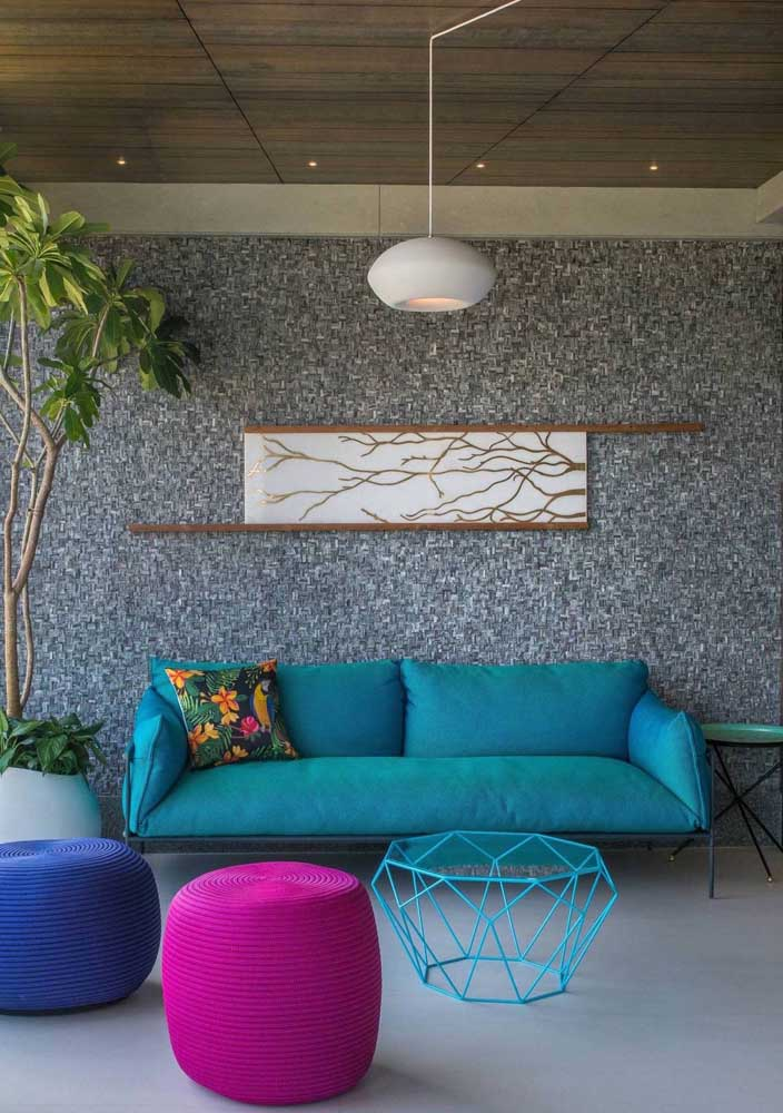 A parede texturizada em cinza se harmonizou muito bem com os elementos coloridos da decoração