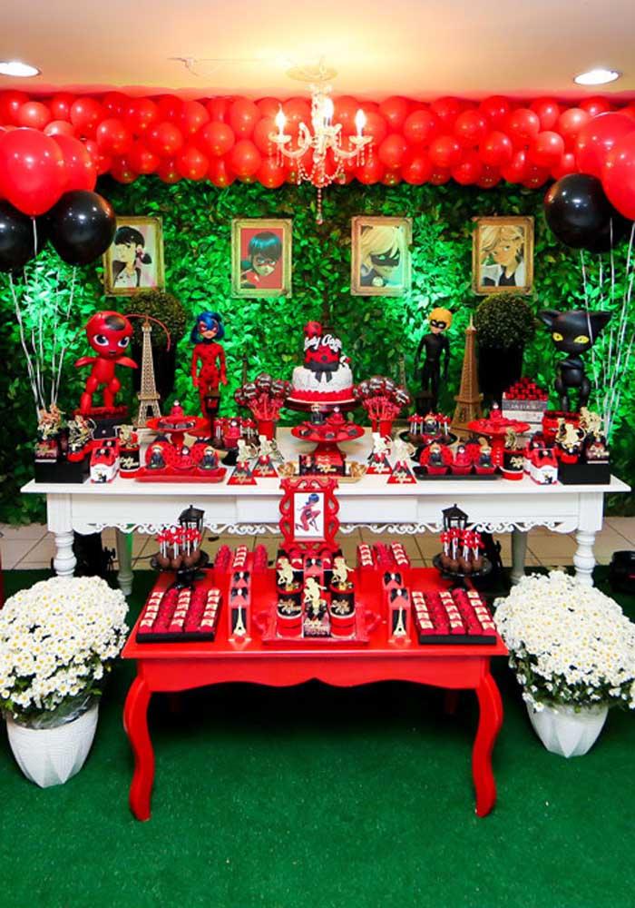 Decoração da mesa do bolo para festa Ladybug. Os tons de vermelho, preto e verde se destacam