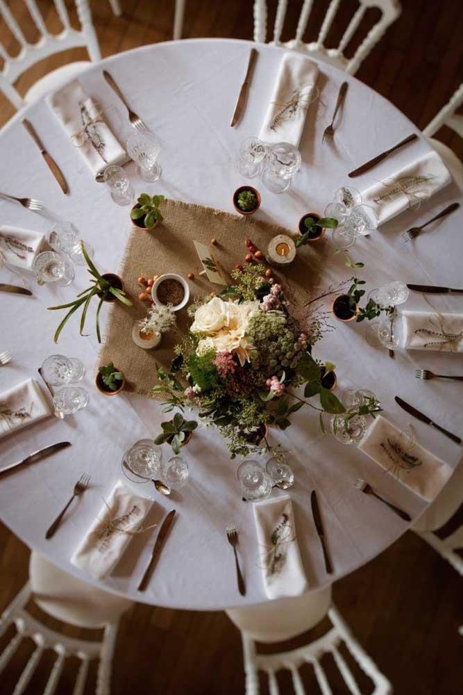 """Nesse casamento, o centro de mesa é um arranjo de flores cercado por pequenos outros vasinhos. Repare que todos eles repousam sobre uma """"toalhinha"""" de juta"""