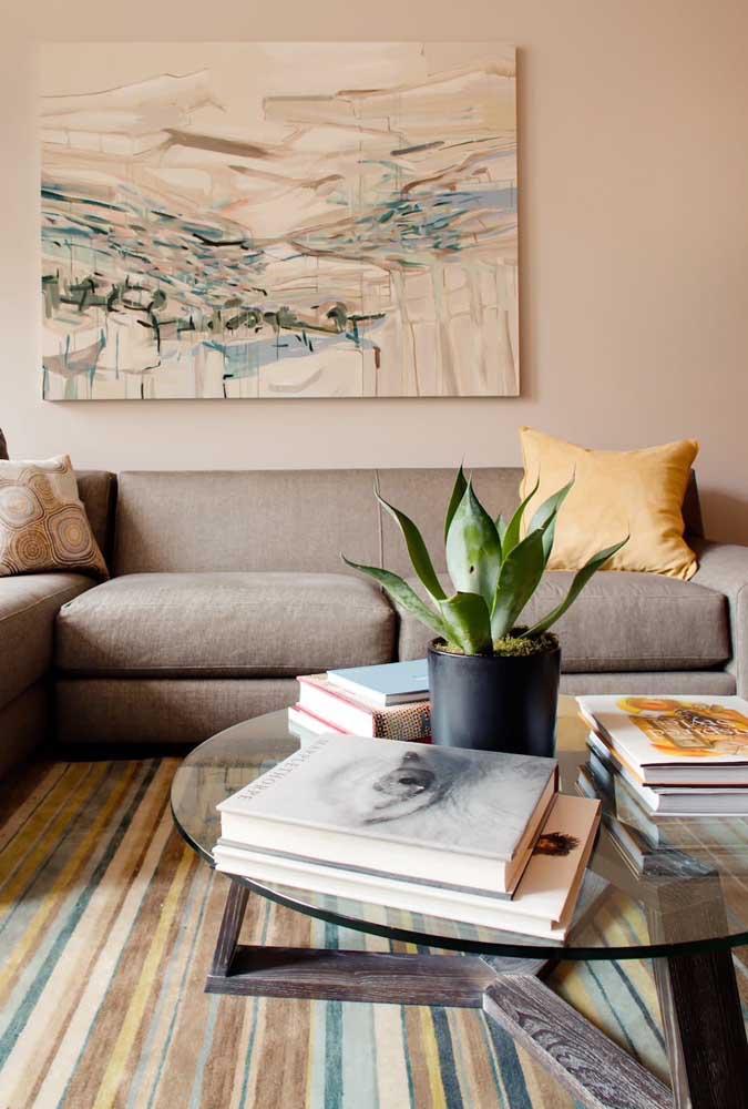 A mesa de centro da sala de estar também merece um enfeite. Aqui, foram usados livros e uma Espada de São Jorge