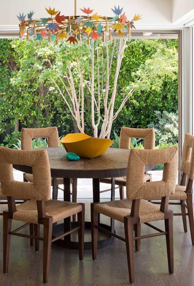 A sala de jantar contemporânea e colorida apostou em um centro de mesa simples, mas marcante