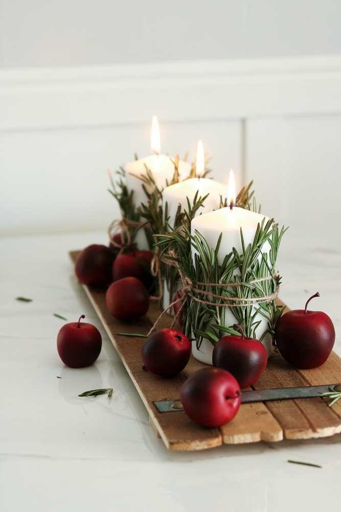 Olha que decoração de natal mais fácil: velas brancas com folhas de pinheiros amarradas pelo cordão de juta. A tabua de madeira com frutas completa a proposta rústica do arranjo