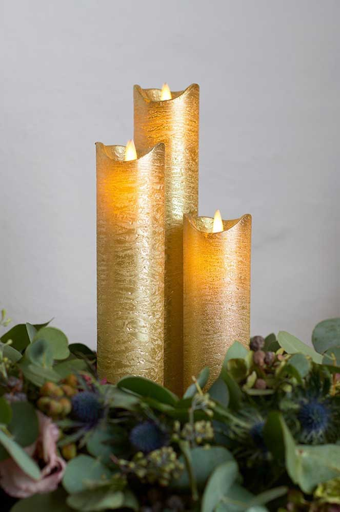 Velas de natal douradas cercadas pelo arranjo de folhas naturais