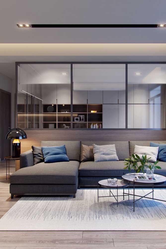 Sobre a mesa de canto, o abajur oferece a luminosidade ideal para a sala de estar