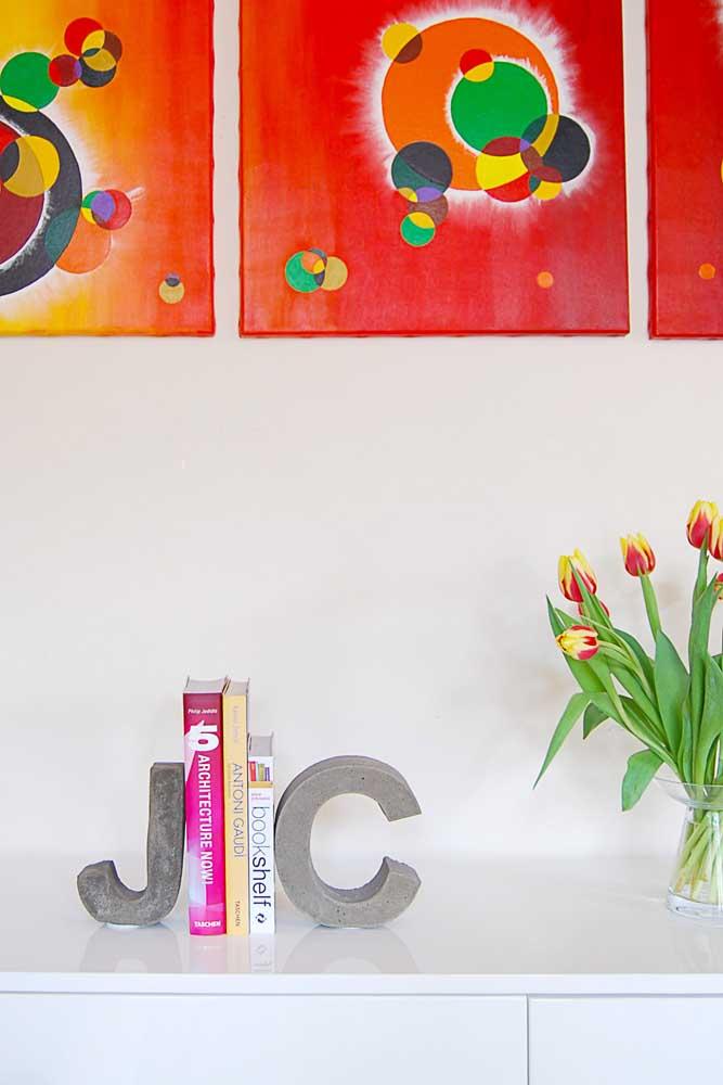 Aqui, as letras decorativas de concreto servem para apoiar os livros na estante