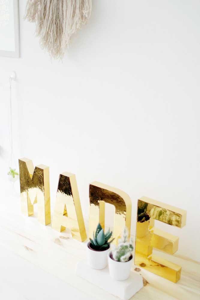 Letras decorativas 3D douradas. Repare como o tom metálico se destaca em meio a decor branca