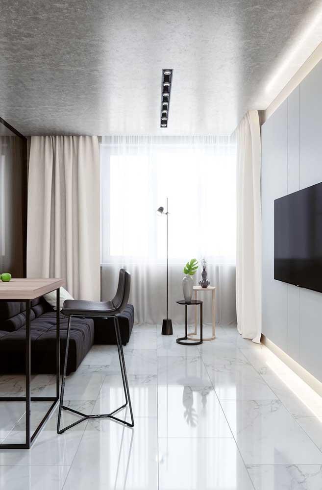 Aqui nessa sala, as placas retangulares de porcelanato branco acompanham o formato do ambiente