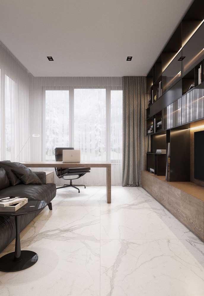 Sofisticação na sala de estar integrada ao home office graças ao piso porcelanato branco marmorizado