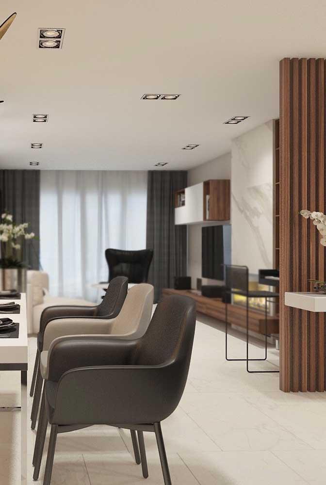Sala de jantar sóbria, neutra e sofisticada. O porcelanato branco oferece a base do projeto