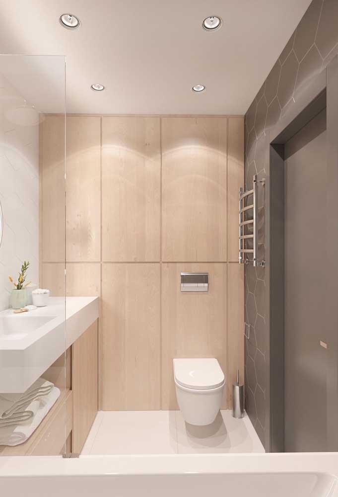 Banheiro clean e muito bem decorado com piso porcelanato branco e painel de madeira