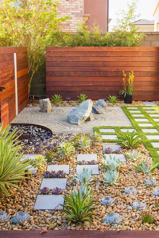 Jardim residencial com cactos, suculentas e areia. Destaque para a fonte de água