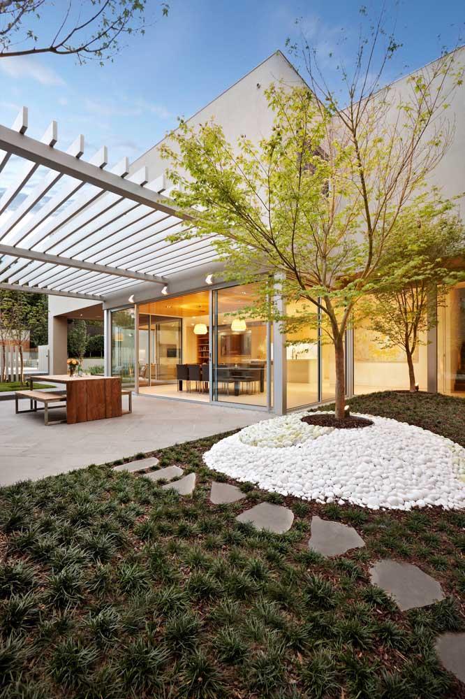 Pergolado e pedras brancas se destacam nesse projeto de jardim residencial moderno
