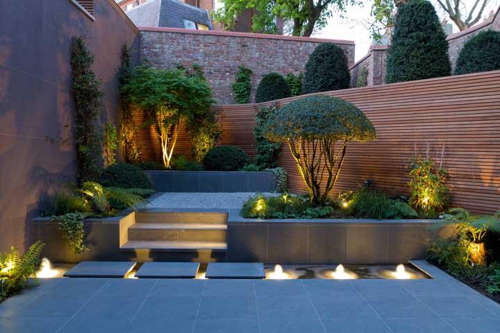 Jardim residencial pequeno emoldurado pelo mini lago iluminado