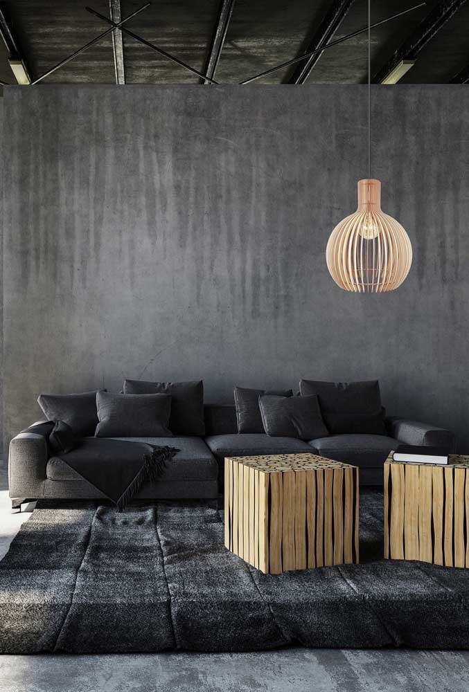 A sala de estar preta ganhou um ponto de luz, literalmente, com o lustre de MDF claro