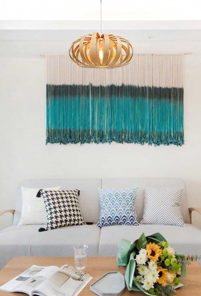 A luz amarela dentro do lustre de MDF deixa a sala de estar mais confortável