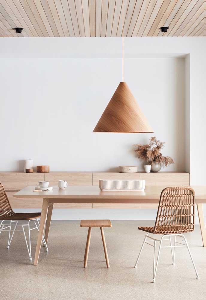 A sala de jantar toda em madeira clara ganhou um lustre de MDF para fechar a composição