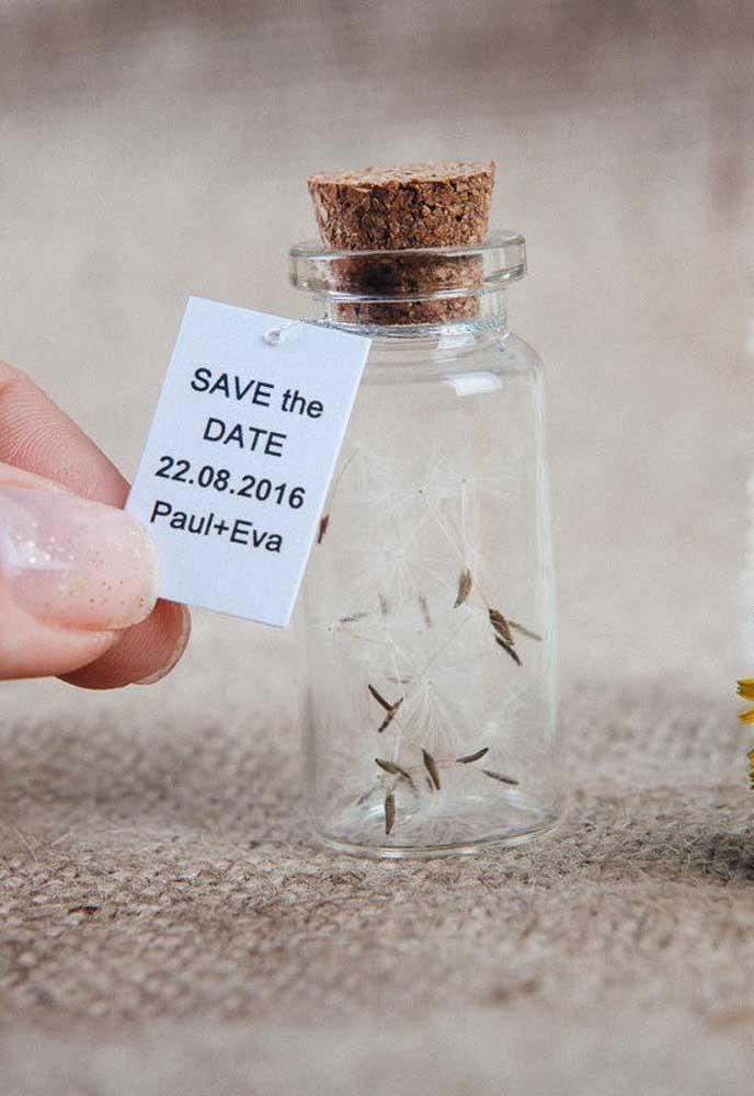 Essa ideia é super delicada e charmosa. O Save the date traz apenas a data e o nome dos noivos junto de um potinho de vidro cheio de pétalas de dente de leão