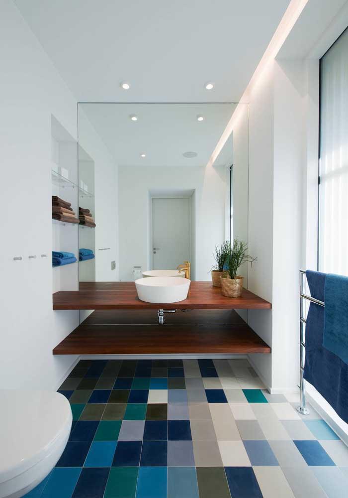 Diferentes tons de tinta epóxi azul colorem o piso desse banheiro