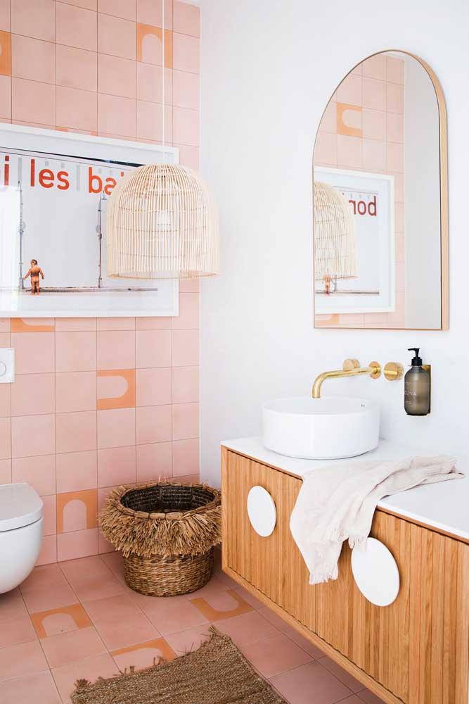 Nesse banheiro, a tinta para azulejo escolhida foi a cor de rosa. Sobre ela, desenhos geométricos em tom de laranja