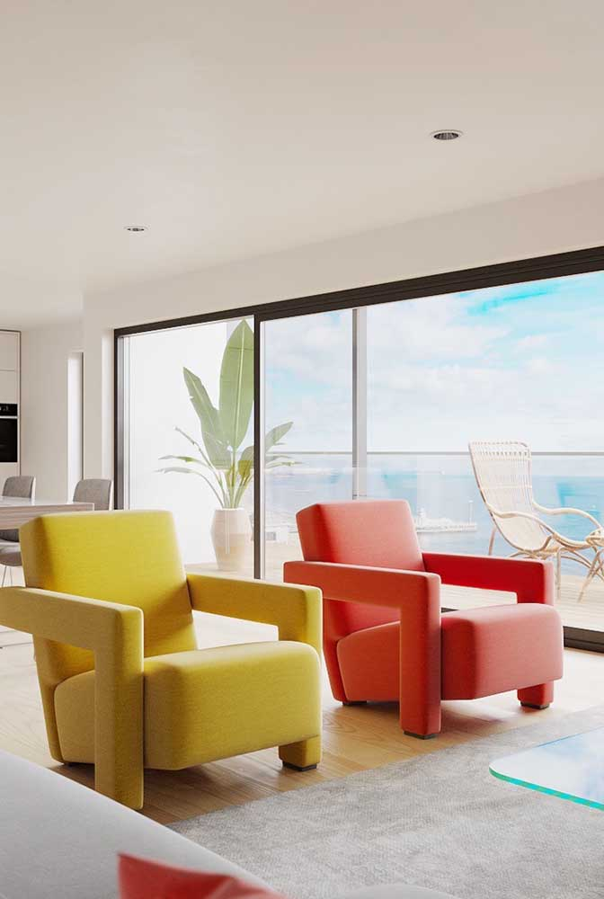 Ambiente moderno e descontraído com a dupla de poltronas decorativas em amarelo e vermelho