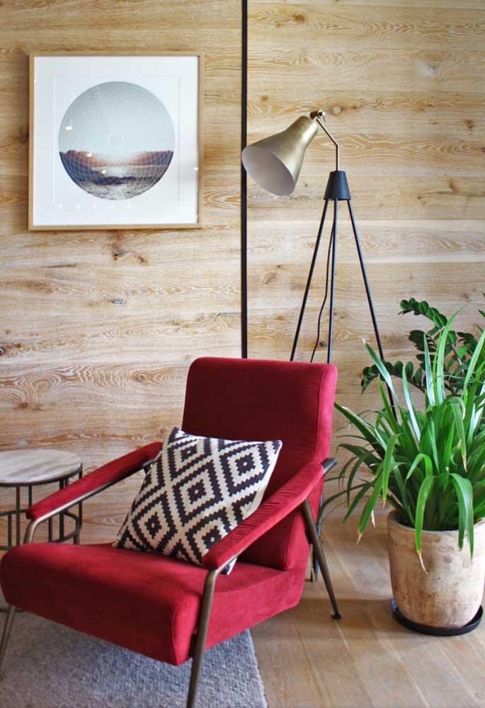 O ambiente com revestimento de madeira ficou ainda mais aconchegante com a poltrona vermelha