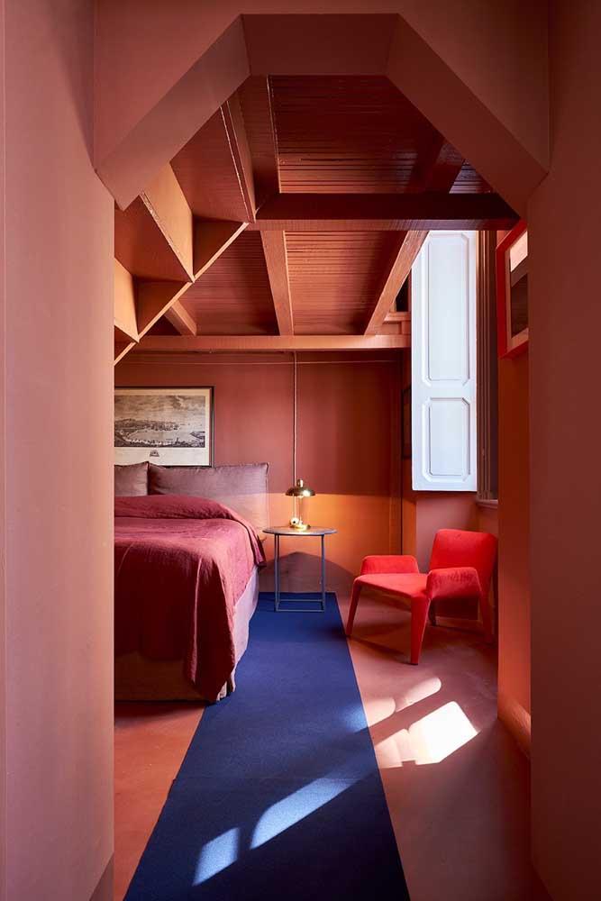 Quarto super conceitual decorado com poltrona vermelha. Repare que o tapete azul trouxe o contraste necessário para o ambiente