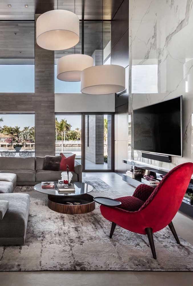 E que tal uma sala de estar decorada em cinza e preto com uma poltrona vermelha?