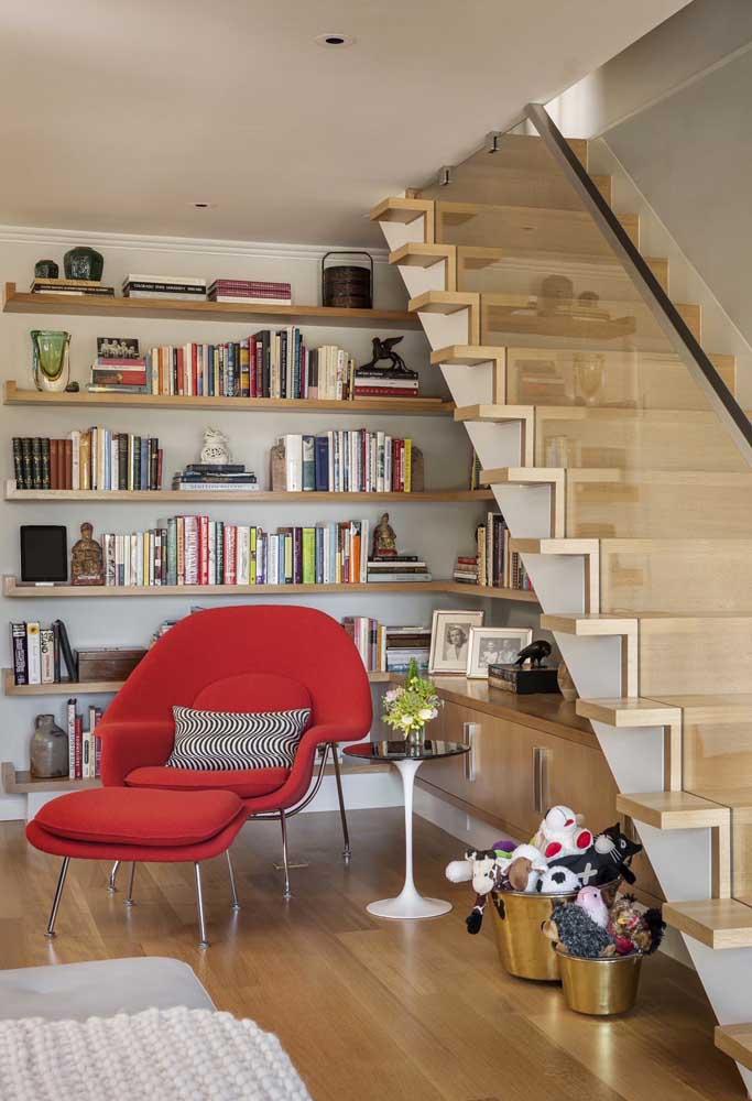 Aqui, a poltrona vermelha integra o espaço embaixo da escada que foi transformado em um cantinho de leitura super aconchegante