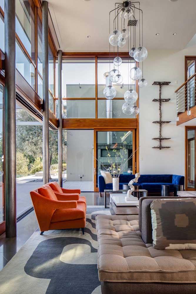 Poltronas vermelhas de um lado, sofá azul do outro. Combinação perfeita para um ambiente moderno e arrojado