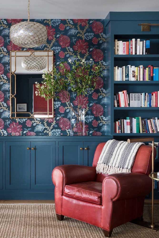 Repare na harmonia visual entre o vermelho e o azul nessa sala. A poltrona em tom queimado se tornou a companheira perfeita do papel de parede e do armário