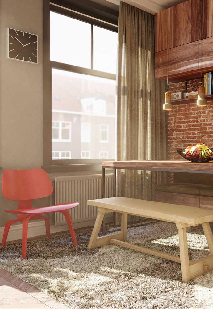 Poltrona vermelha na cozinha. O estilo rústico do ambiente casou como uma luva com a peça