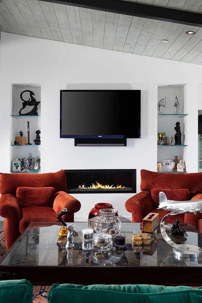As poltronas vermelhas de veludo completam o clima aconchegante da sala de estar com lareira