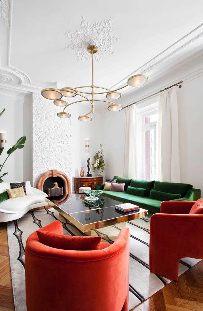 Uau! E o que acha dessa composição aqui? Sofá verde com poltronas vermelhas. O fundo branco realça a combinação