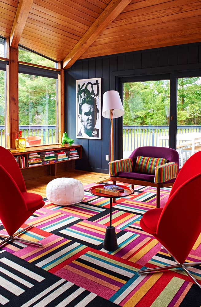 Uma sala de efeito! Aqui, a composição super colorida e listrada apostou no visual impactante das duas poltronas vermelho escarlate