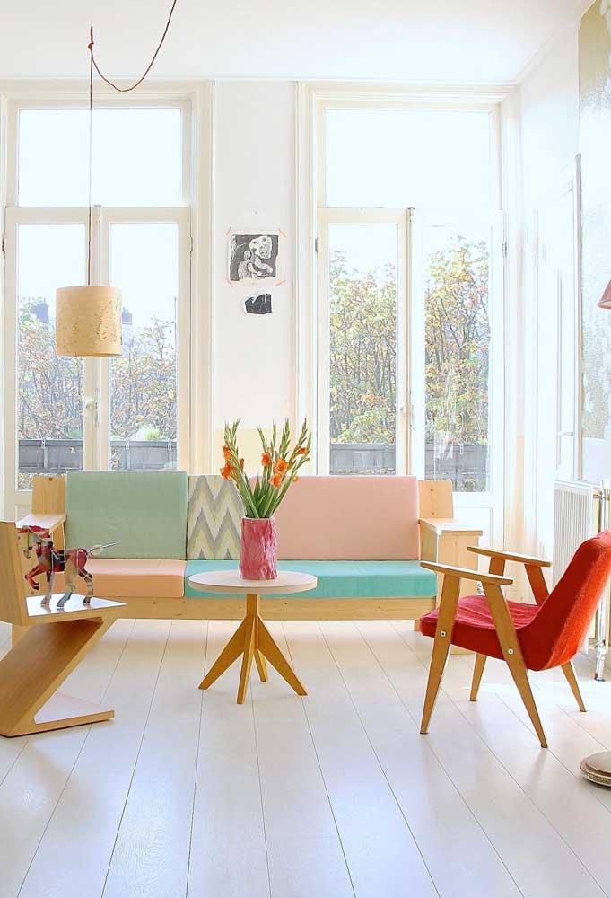 Essa sala banhada pela luz natural traz uma poltrona vermelha moderna para combinar com a marcenaria de cor clara